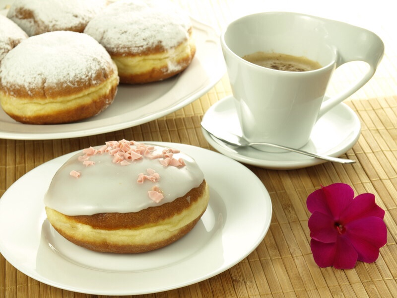 Cup of coffee with frosted donuts.