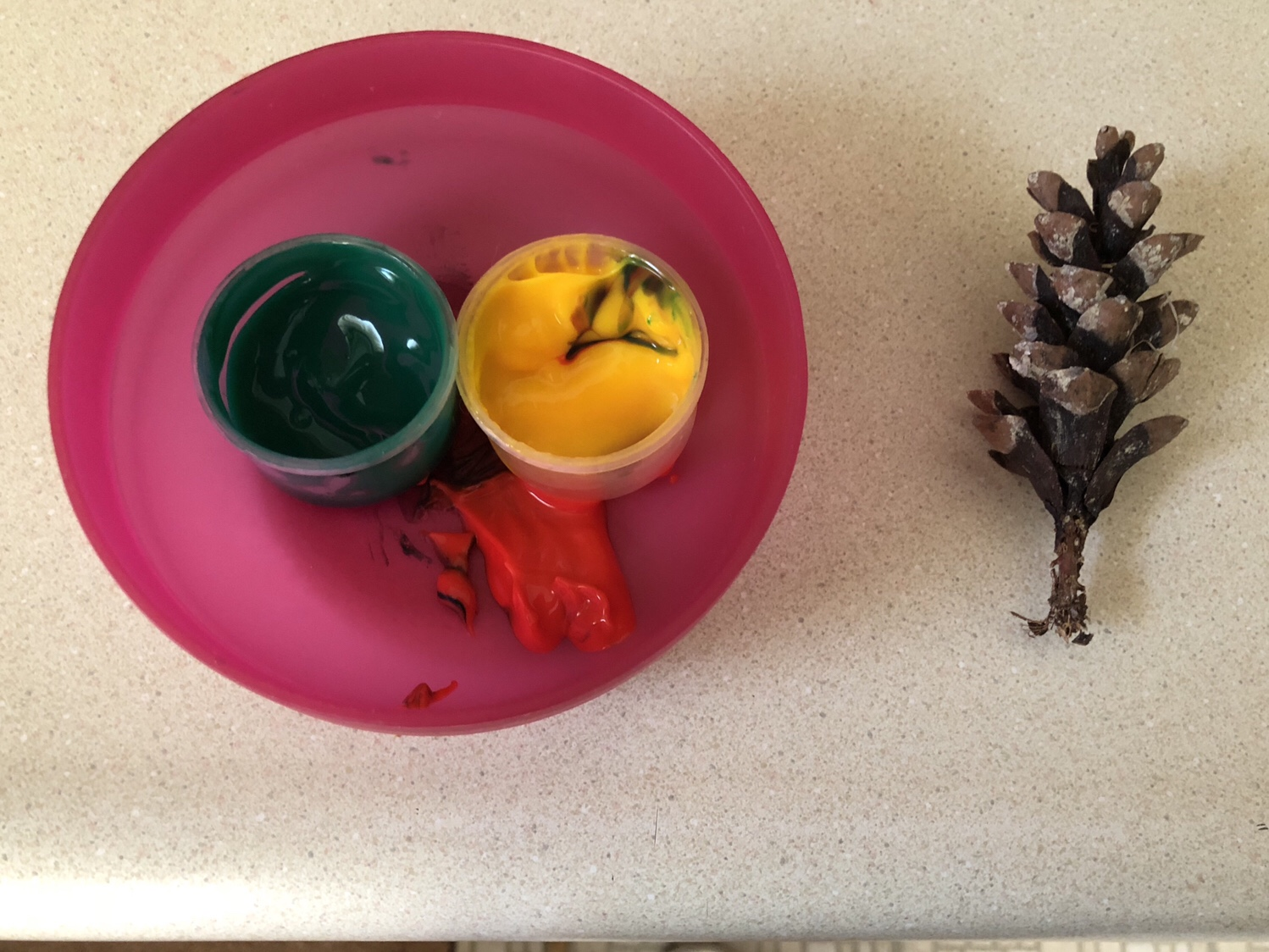 Different colored paints with a pinecone