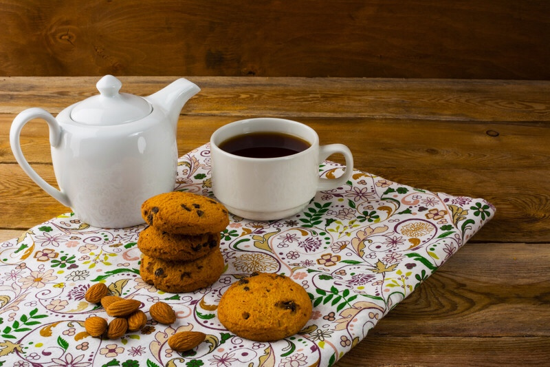 A cup of tea with a tea pot and pastries.
