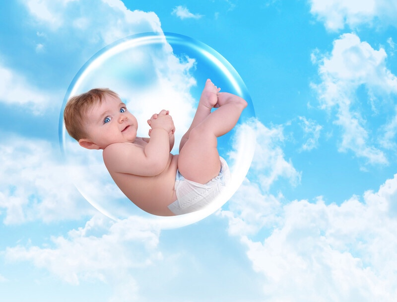 A baby floating inside a protective bubble in the clouds.