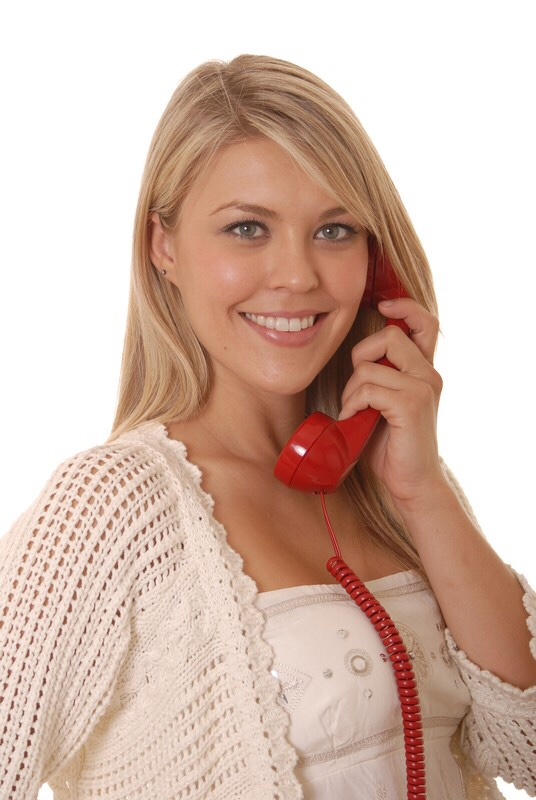Girl talking on corded phone.
