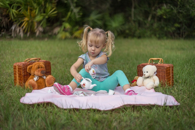 A toddler having a picnic with her teddy bears.