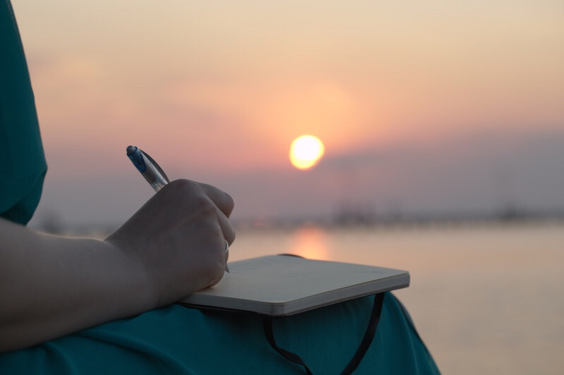 A woman's hand writing in a diary with the ocean and sunset in the background.