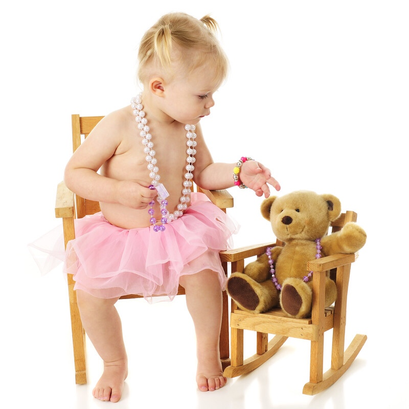 A toddler wearing beads and putting a necklace on her bear.