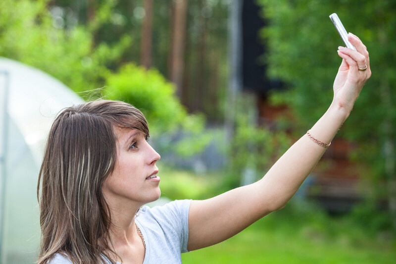 Woman holding up cell phone looking for coverage.