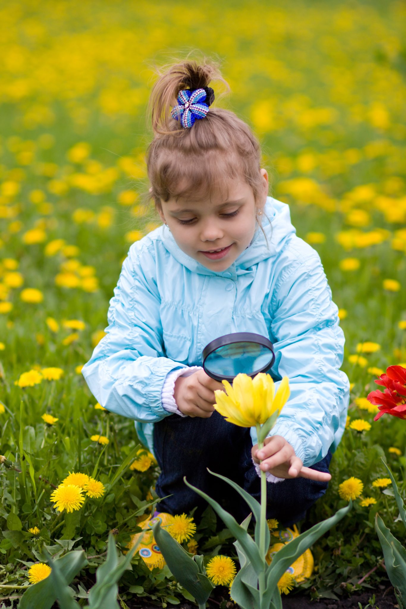 Girl looking at flower through magnifying glass.
