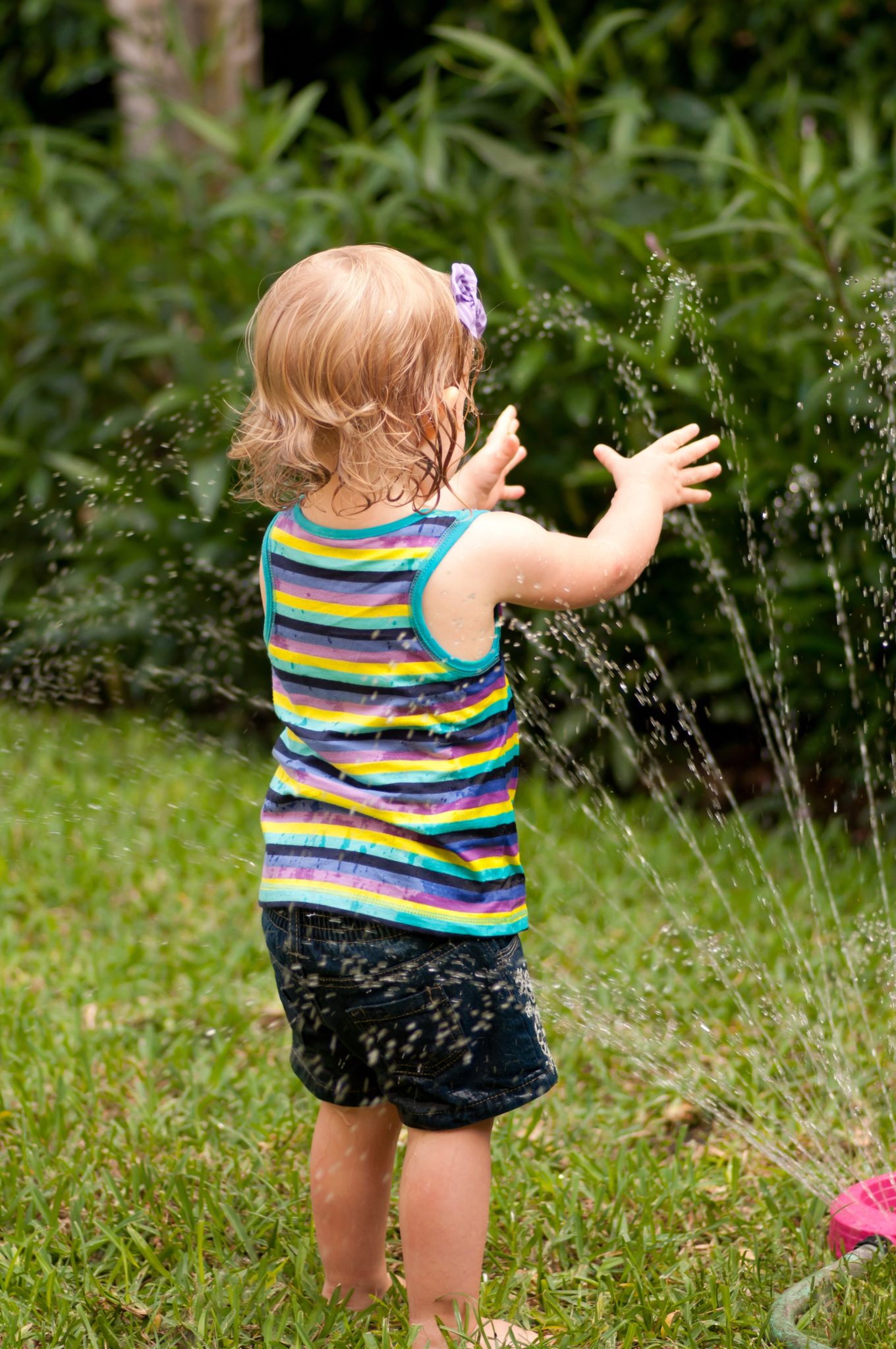 Little girl playing with hose.