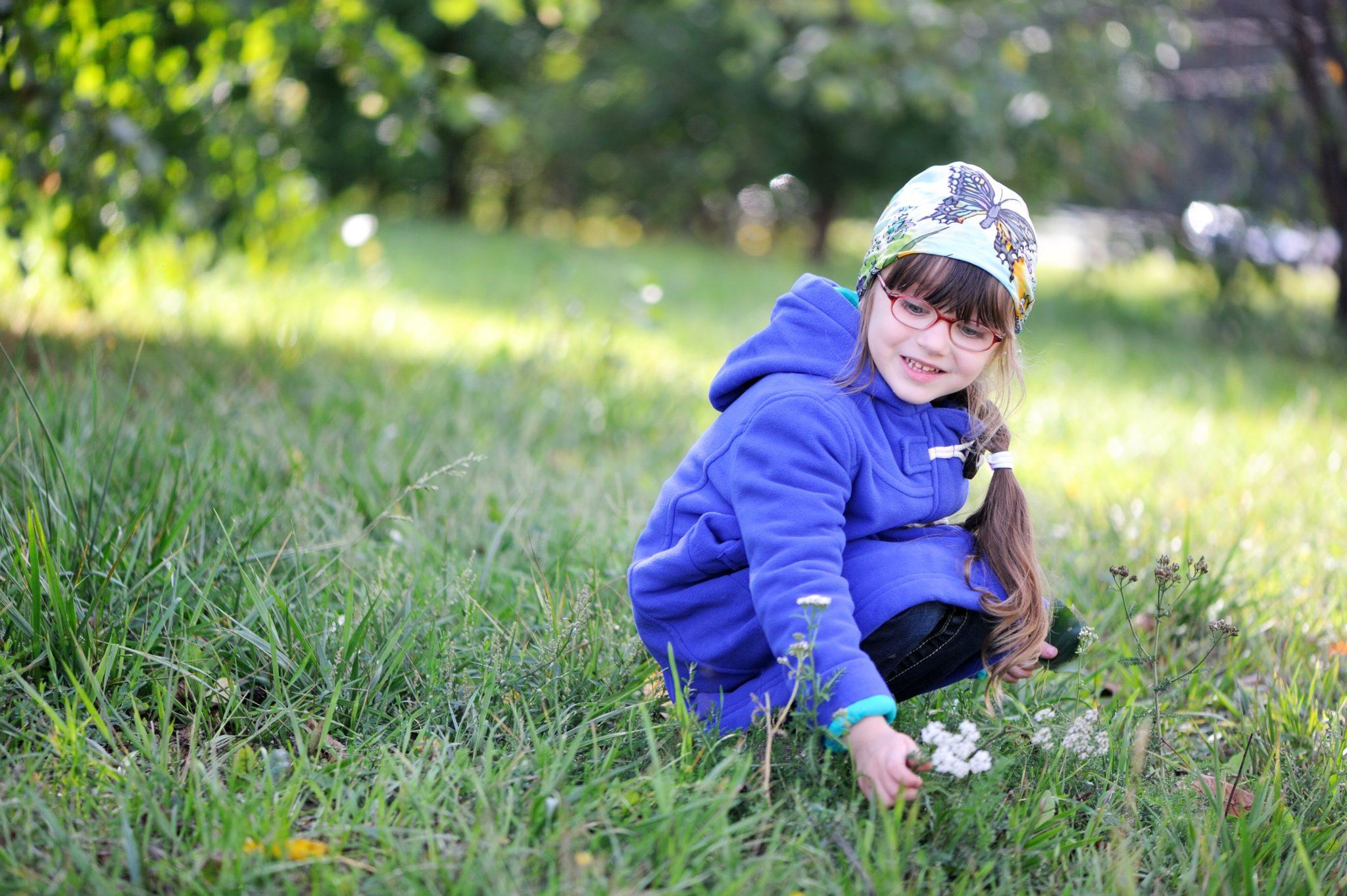 Little girl picking up flower.