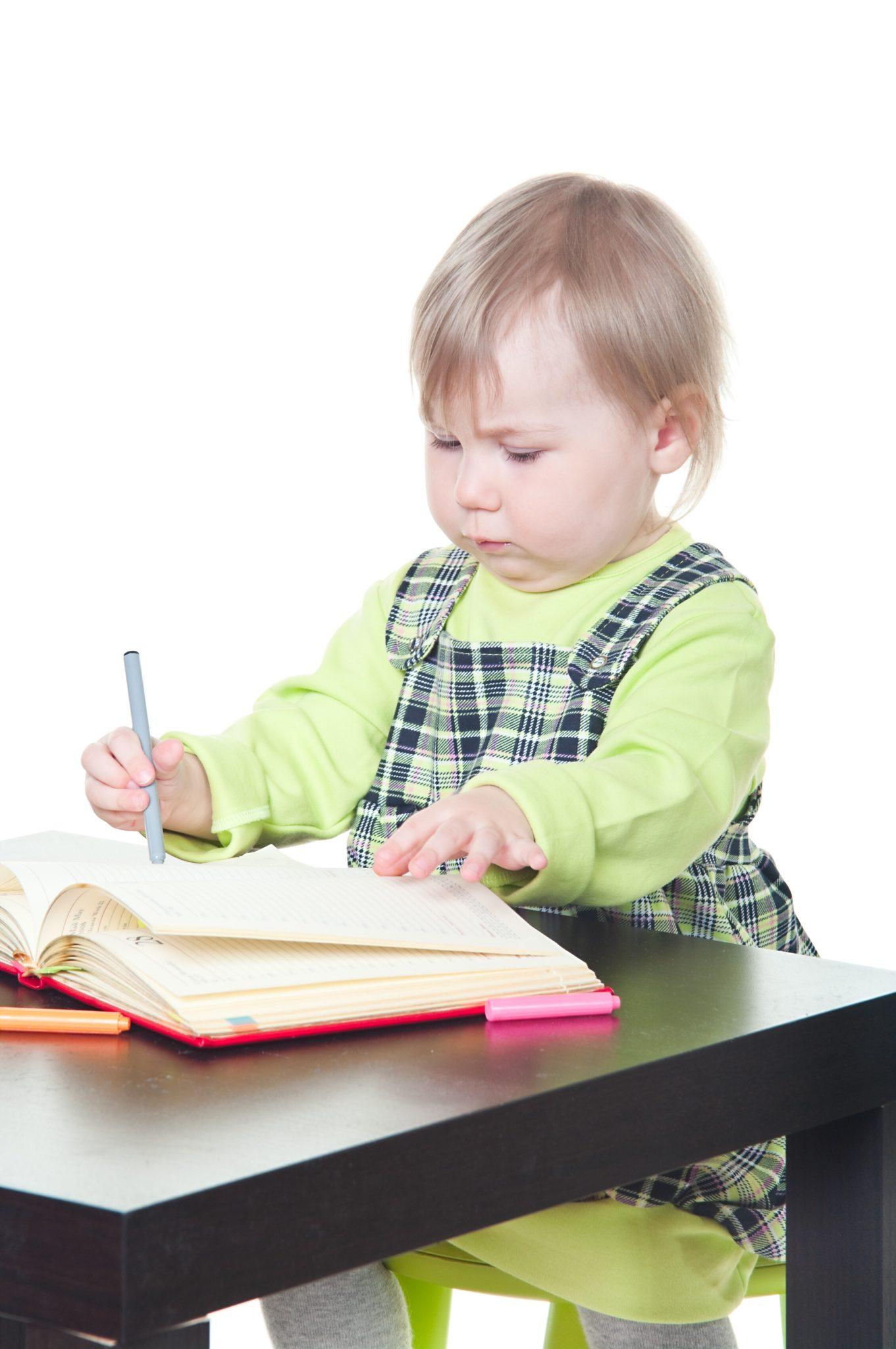 Girl drawing in book.