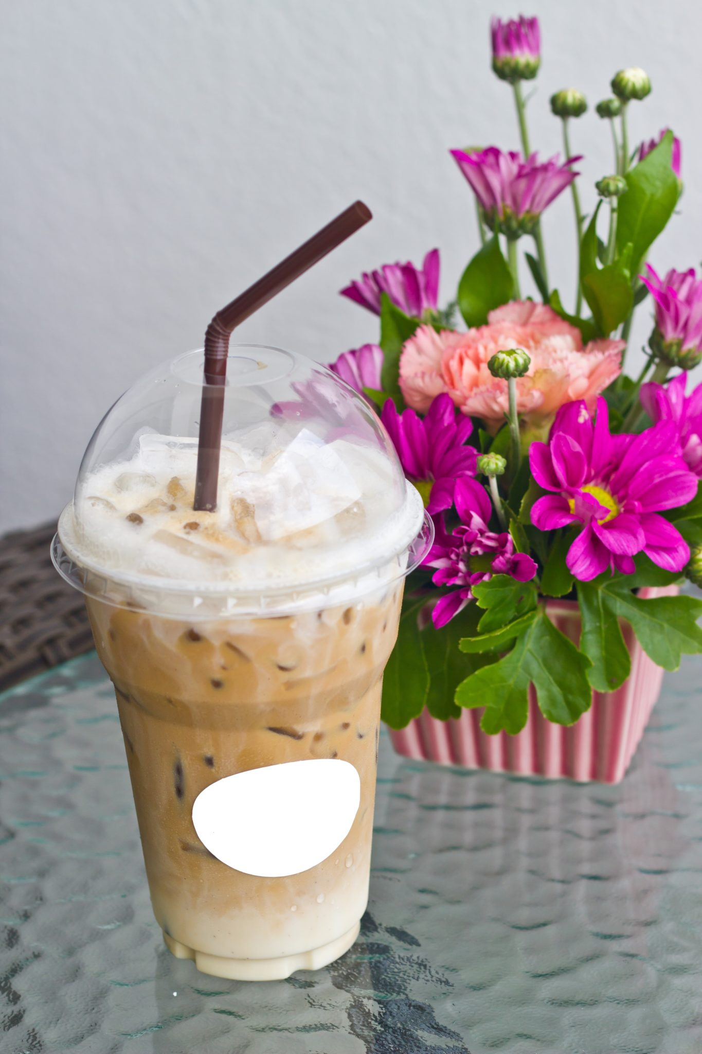 Iced coffee with a vase of flowers.