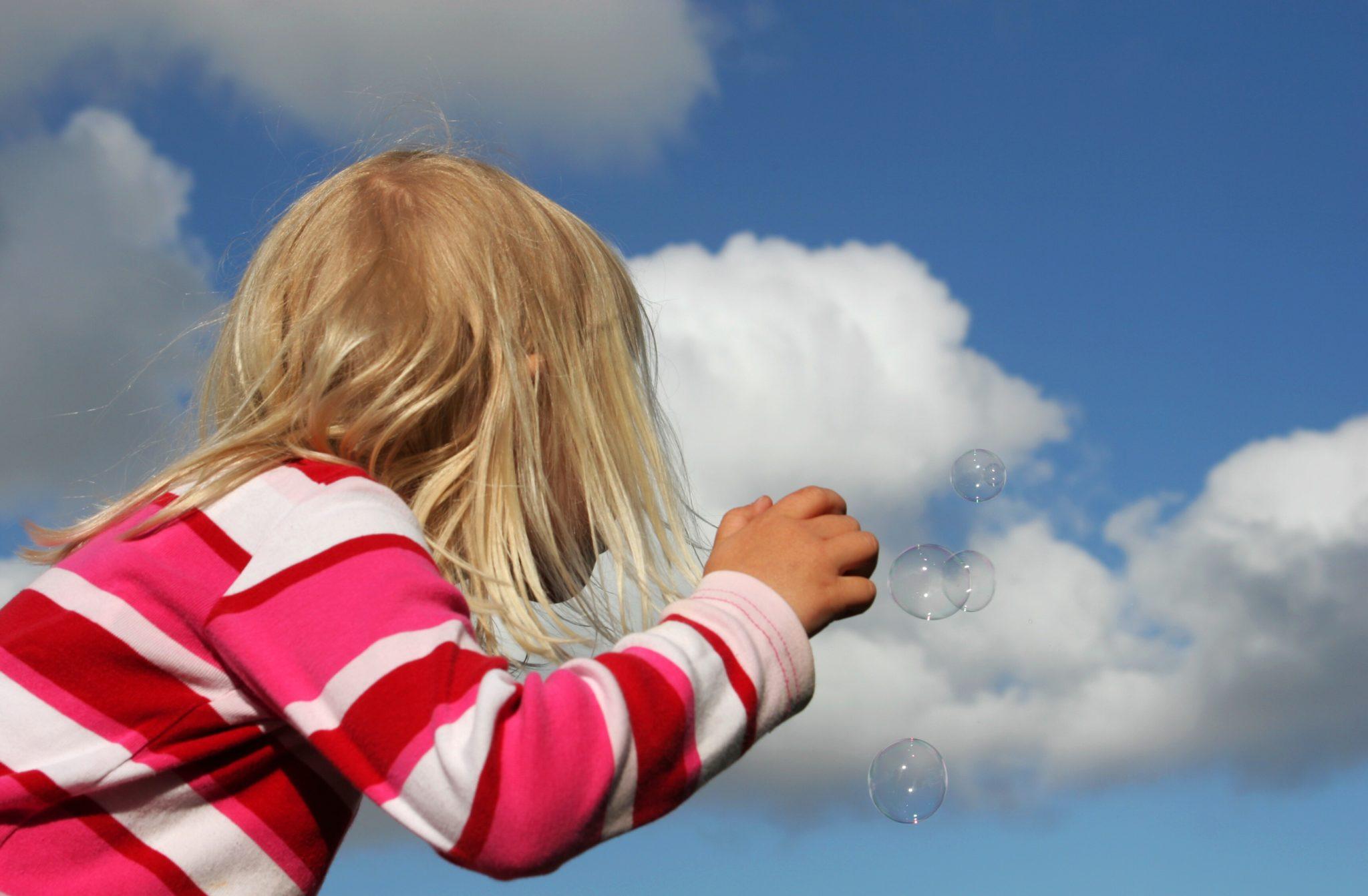 Little girl blowing bubbles.