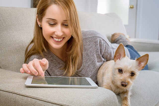 Woman using tablet relaxing next to her dog.