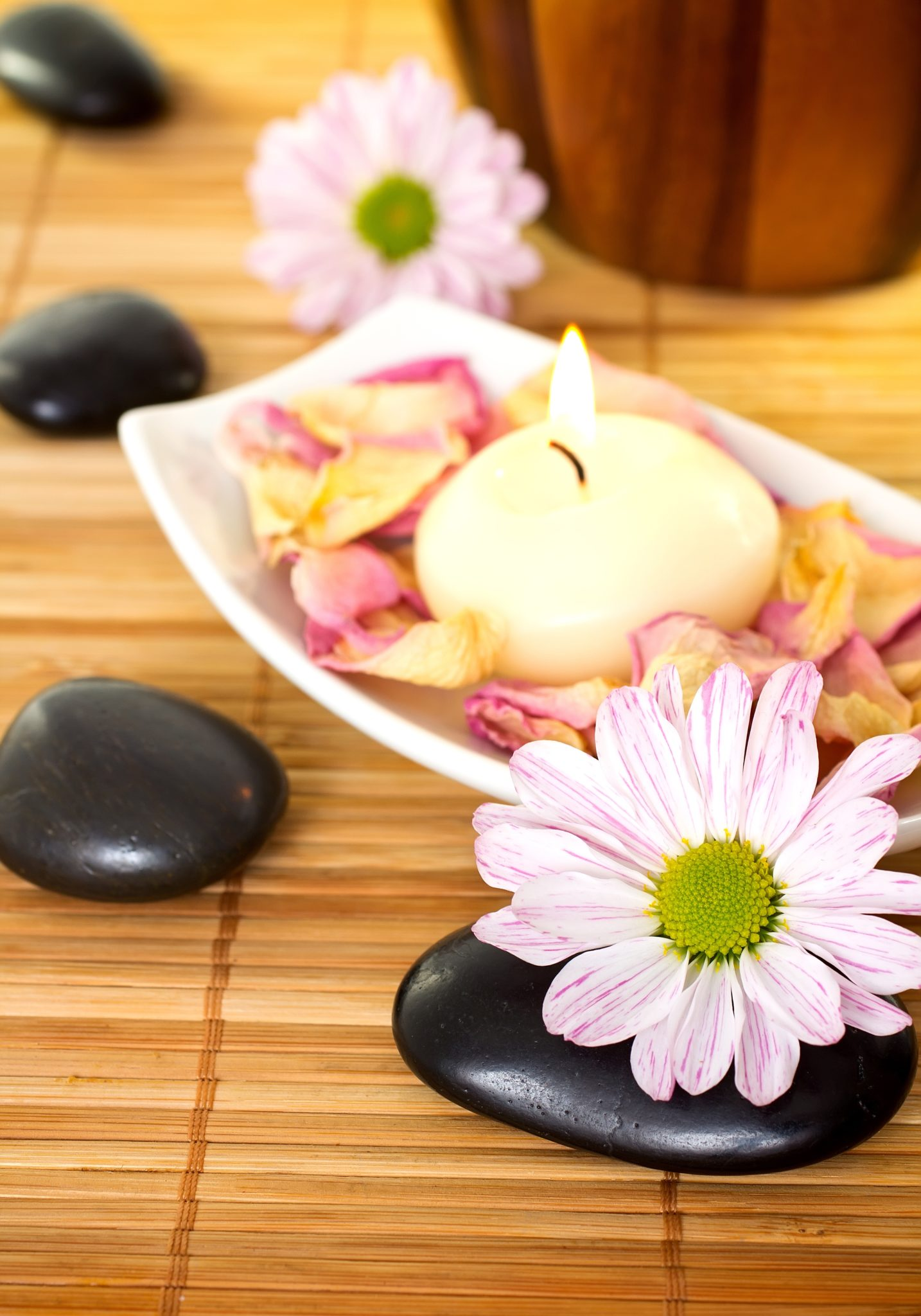 Spa treatment with stones, candles and flowers.