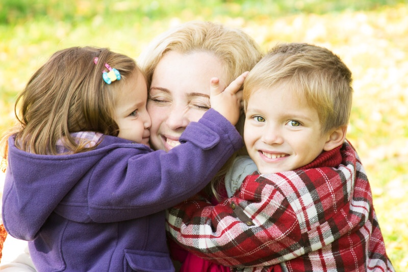 Mother hugging two children