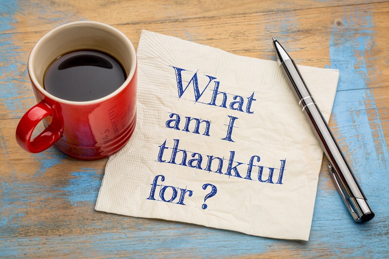 A coffee cup next to a napkin with text, what am I thankful for?