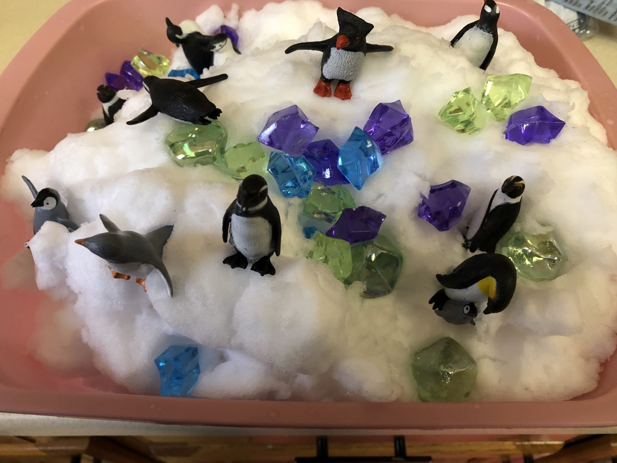 Snow sensory tub with stones and penguins