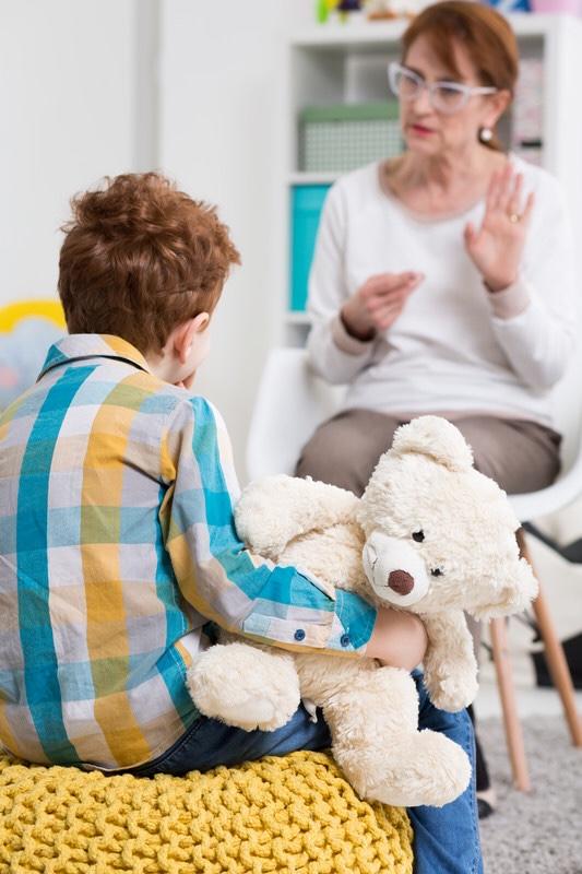 Woman teaching boy sign language
