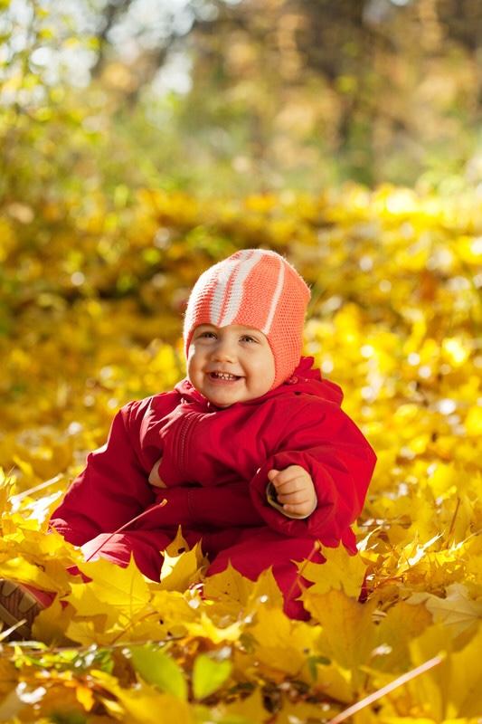 Toddler girl sitting in leaves