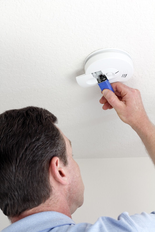 A man replacing the batteries in a smoke detector for home safety