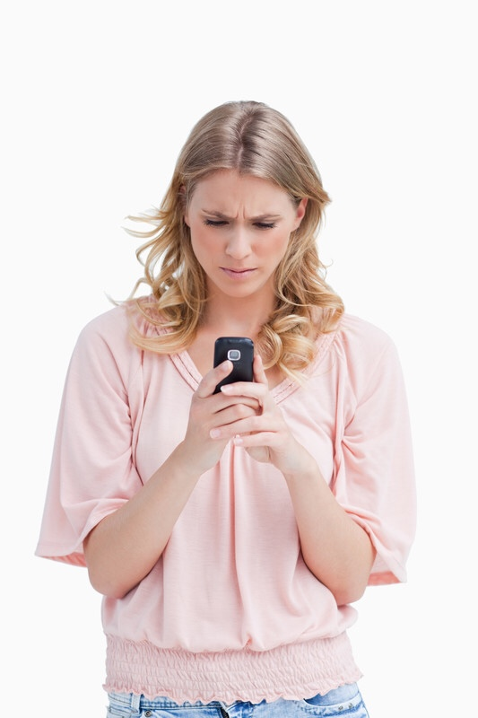 Concerned woman looking at cell phone.