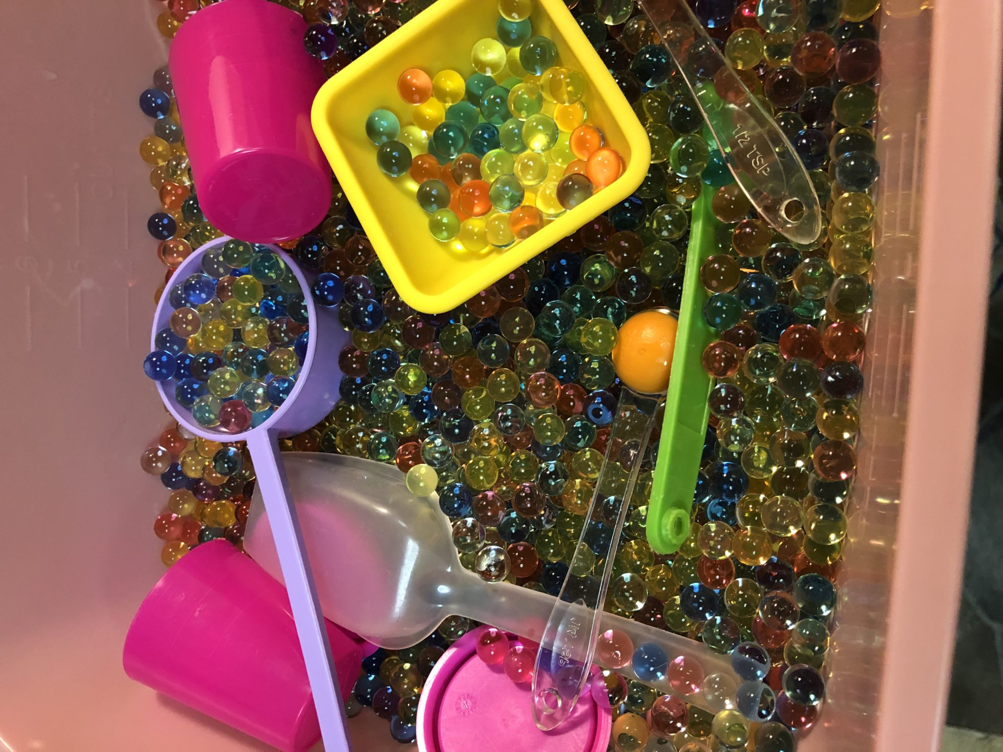 Sensory tub with water beads, scoops and cups.
