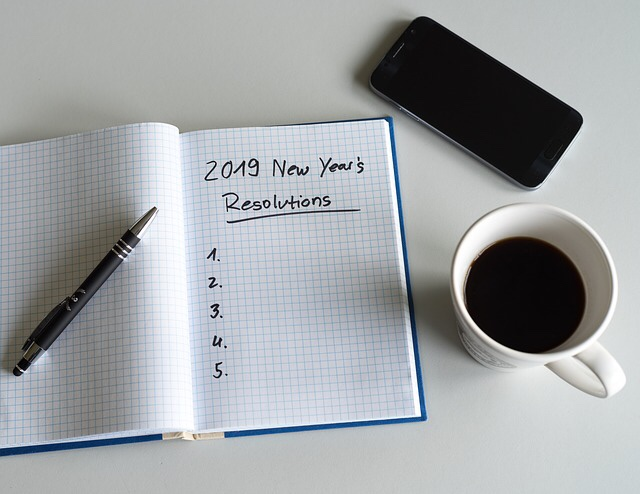 2019 New Years Resolutions written in a notebook with cup of coffee