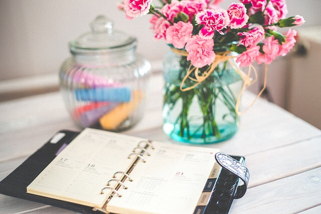 Planner on a desk with flowers