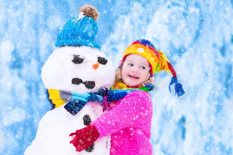 Toddler girl playing with snowman
