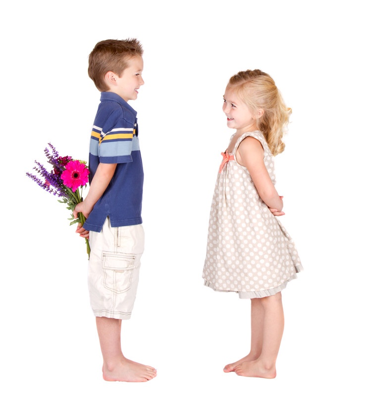 Girl looking at boy with flowers behind his back