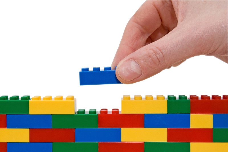 Hand building wall with legos. Brick by brick.