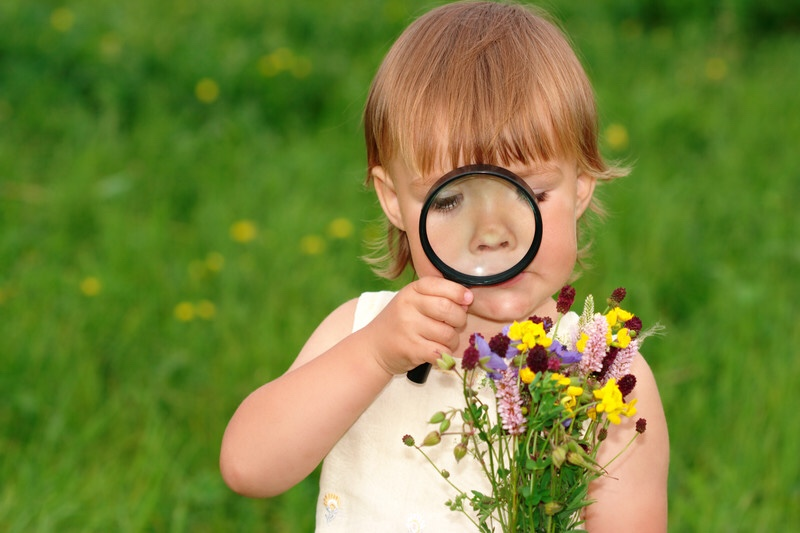 Girl looking at flowers through magnifying glass. Curiosity and discovery.