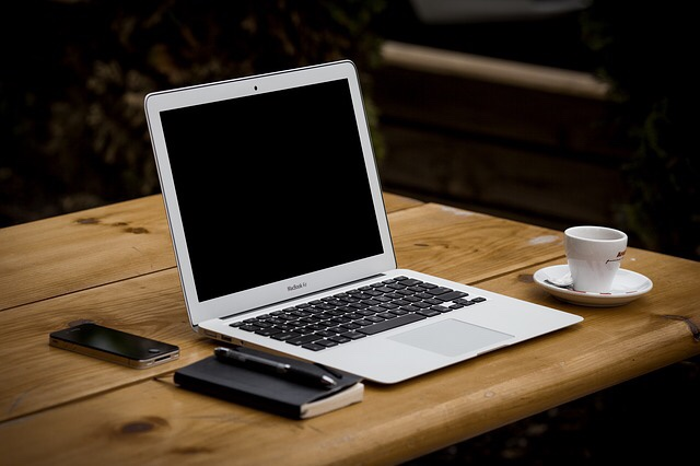 A mac book on a desk next to a cup of coffee.