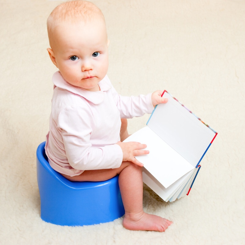Toddler on the potty with an open book.