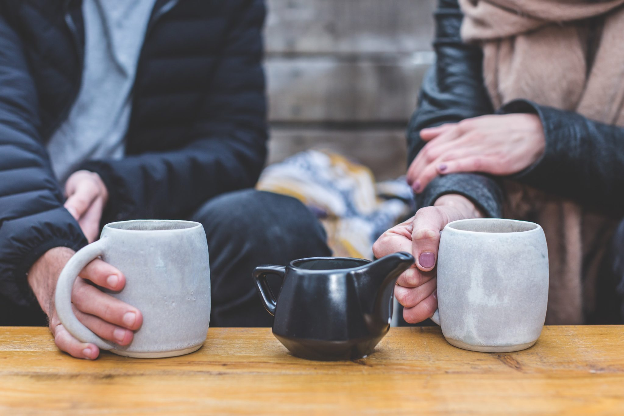 Couple with cups of coffee and creamer between them