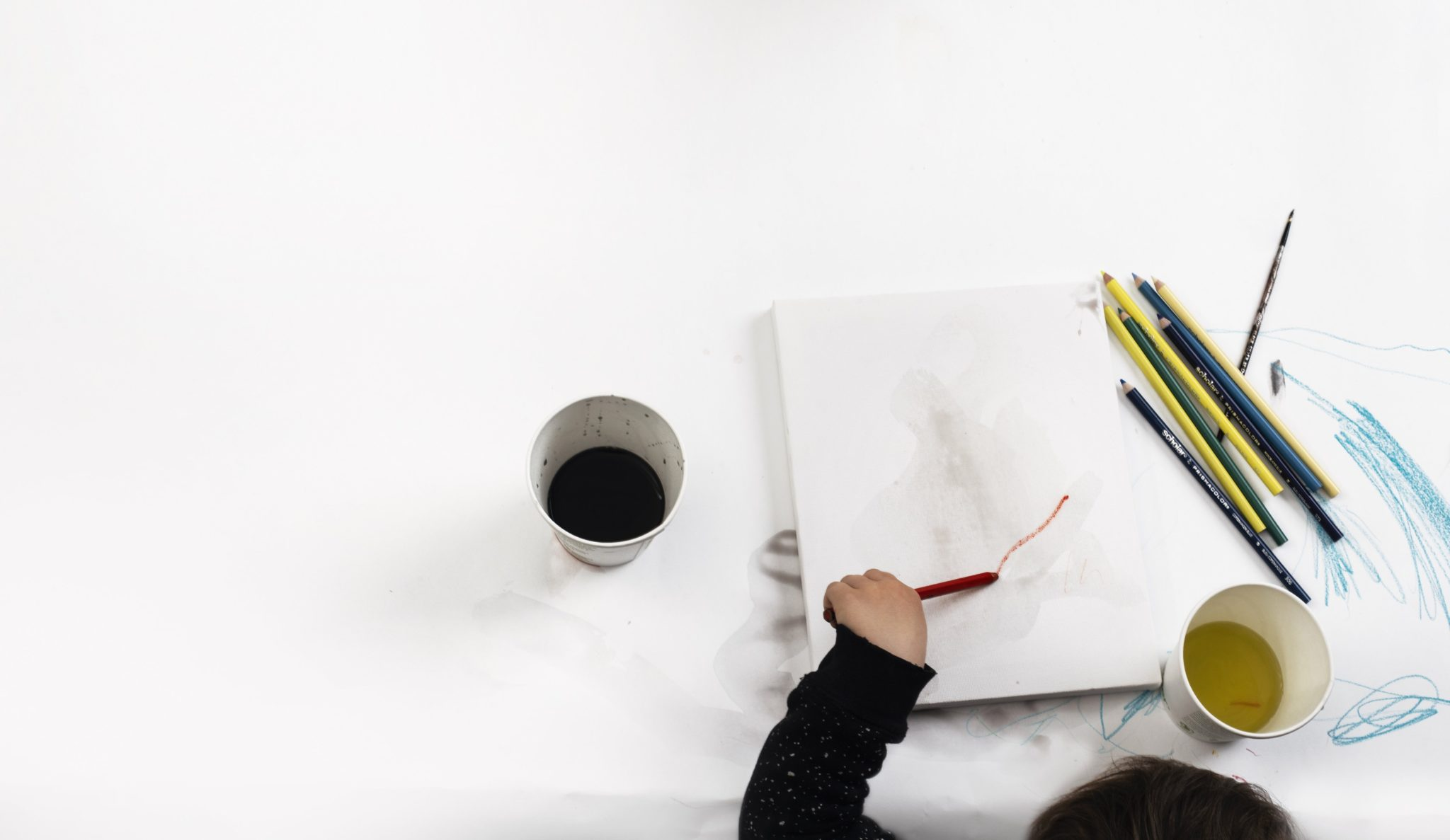 Child painting with art supplies