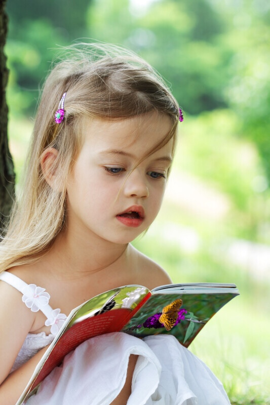 Little girl under tree reading book