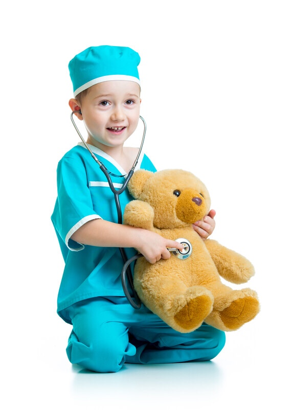 Toddler playing doctor with a teddy bear