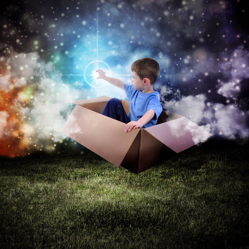Boy floating in cardboard box reaching for a glowing star.