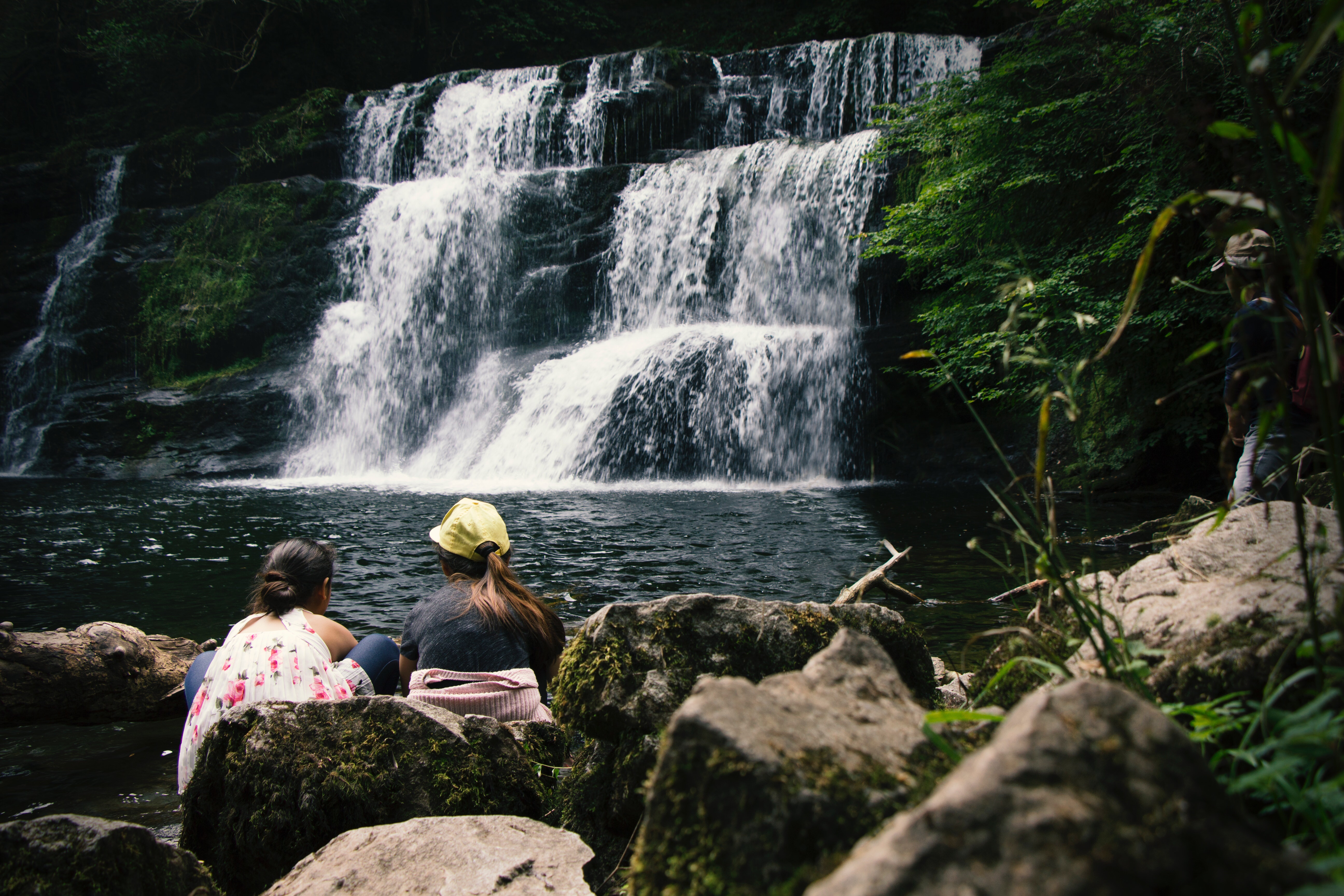 Two women sit in front of waterfall