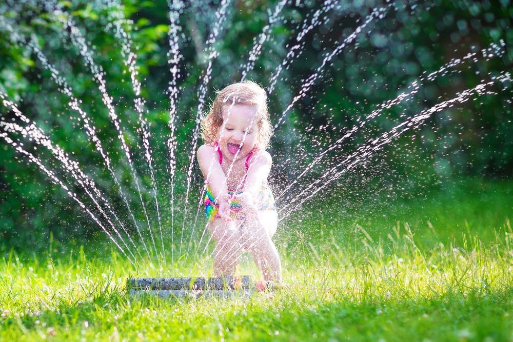 Little girl playing with sprinkler