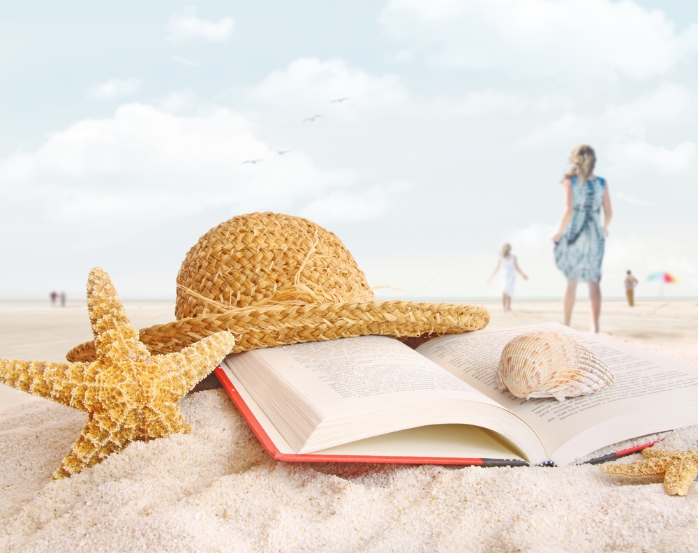 Sea shells, a hat and a book on a beach