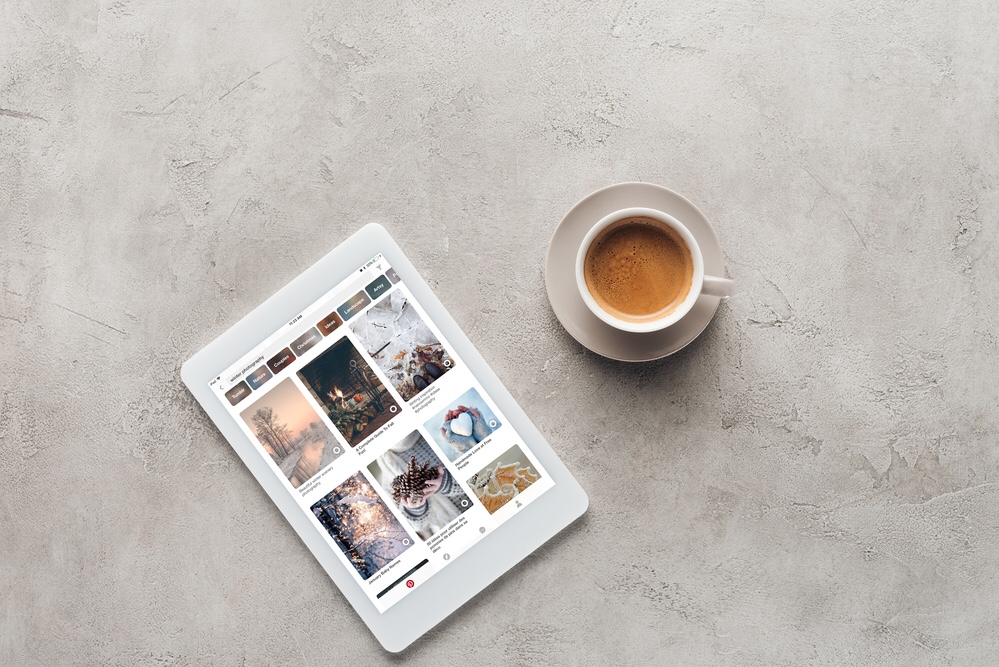 Coffee cup and a tablet with Pinterest on screen
