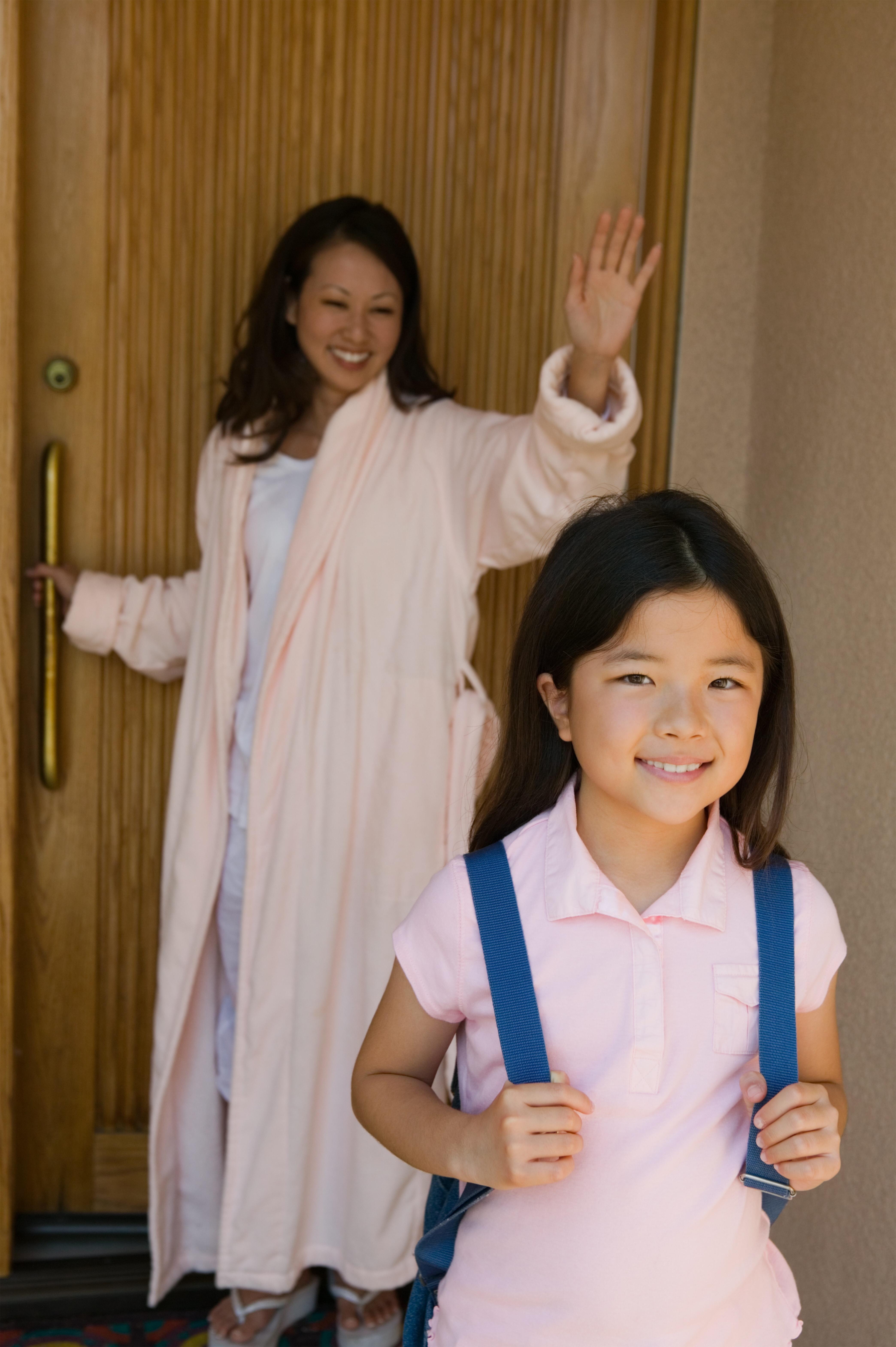 Mother waving daughter off to school