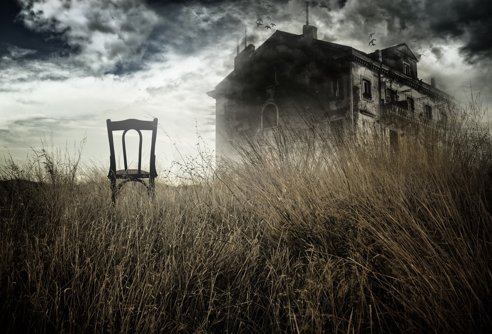 A single chair faces a haunted house