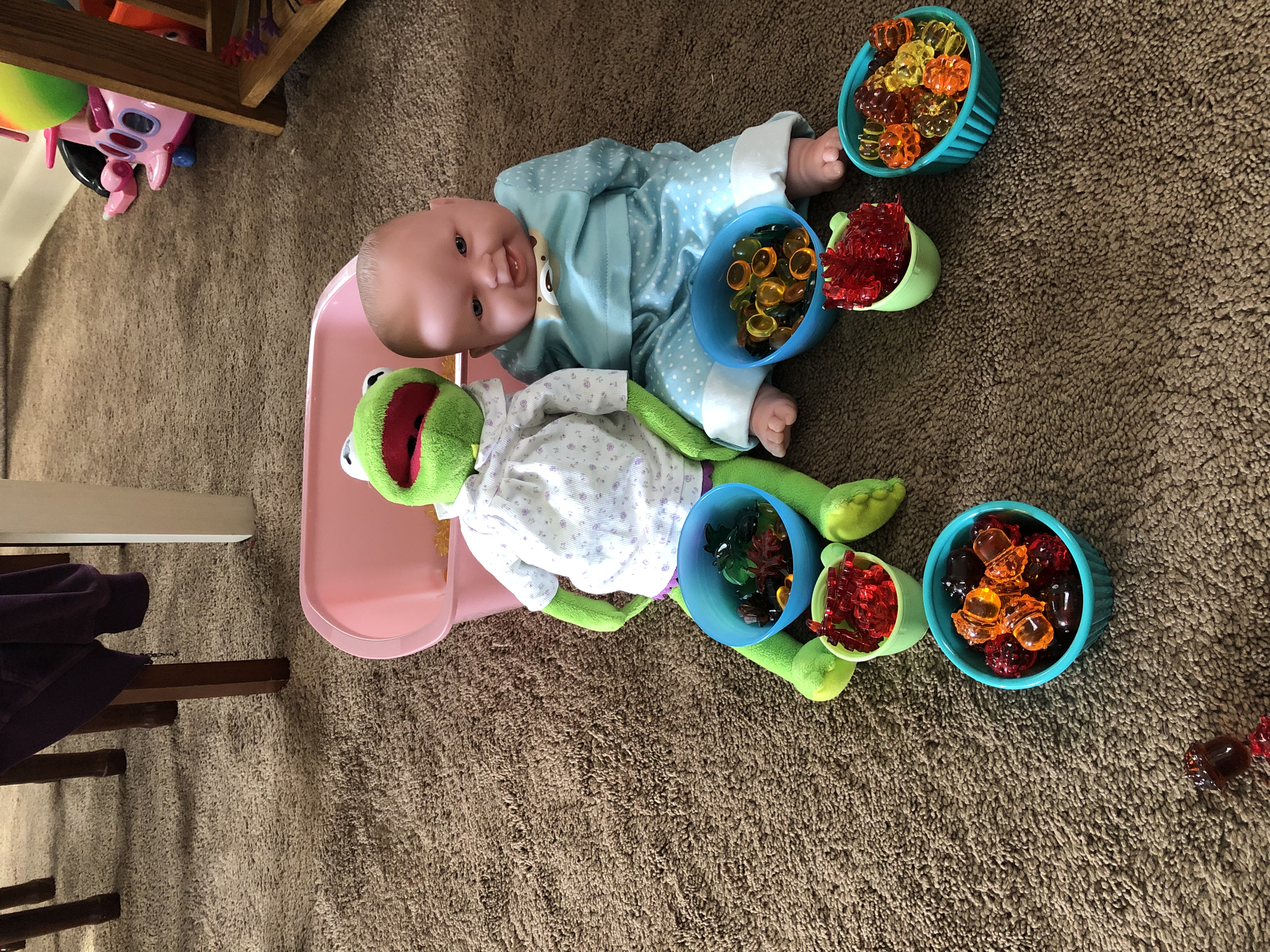 A baby doll and Kermit with bowls of Halloween items.