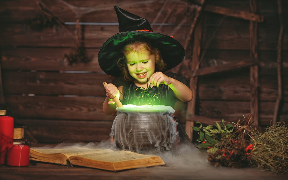 Child witch cooking magic potion in caldron