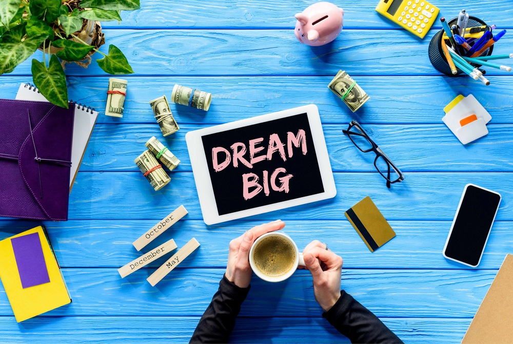 Coffee on a desk with a tablet that says, dream big.