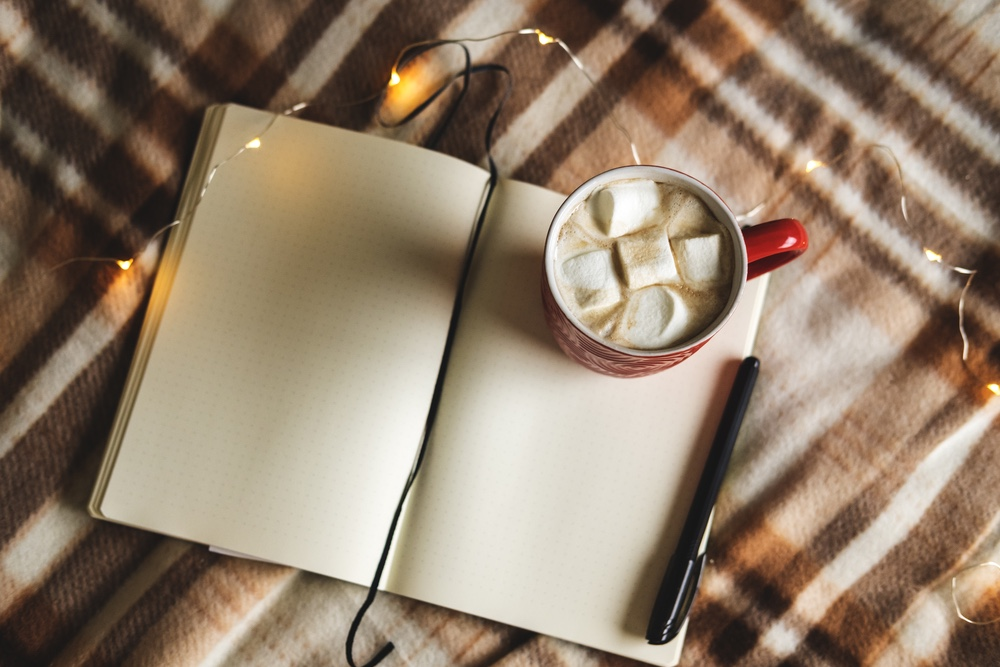 A cozy winter place to journal. A mug of hot chocolate next to a notebook.