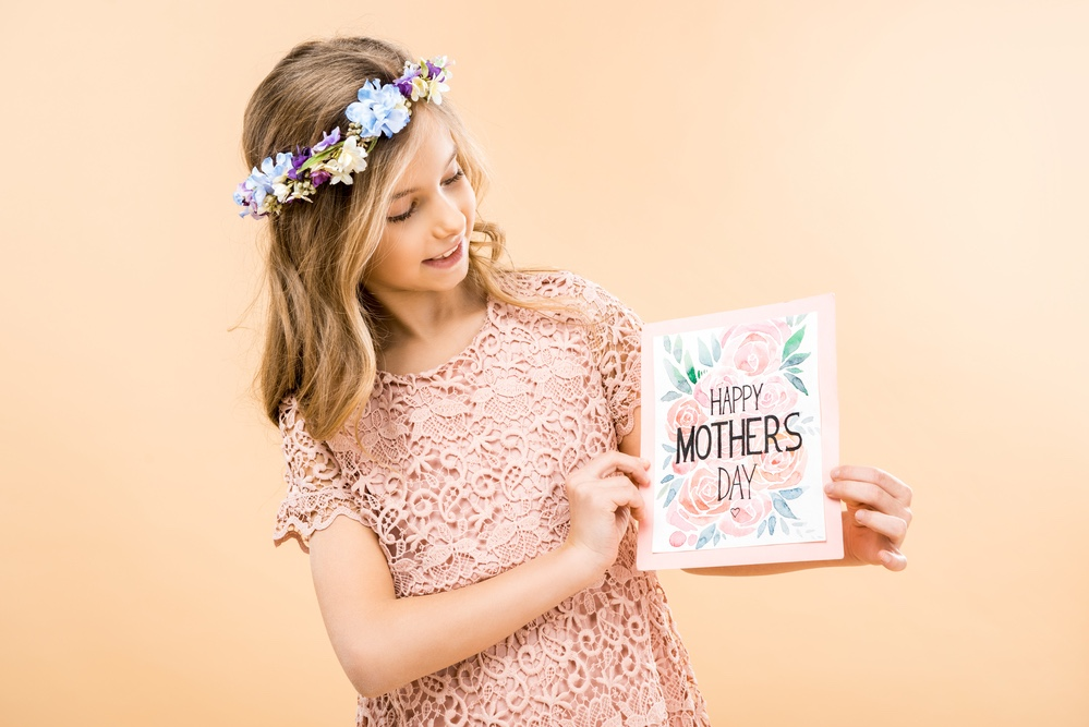 Girl in pink dress with Mother's Day card.